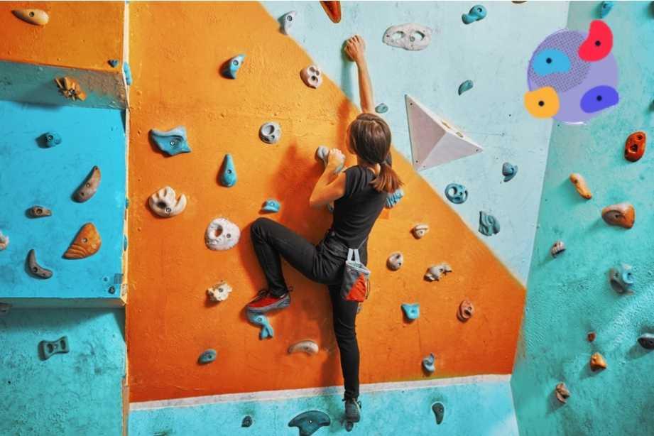 Meisje klimt op oranje klimmuur