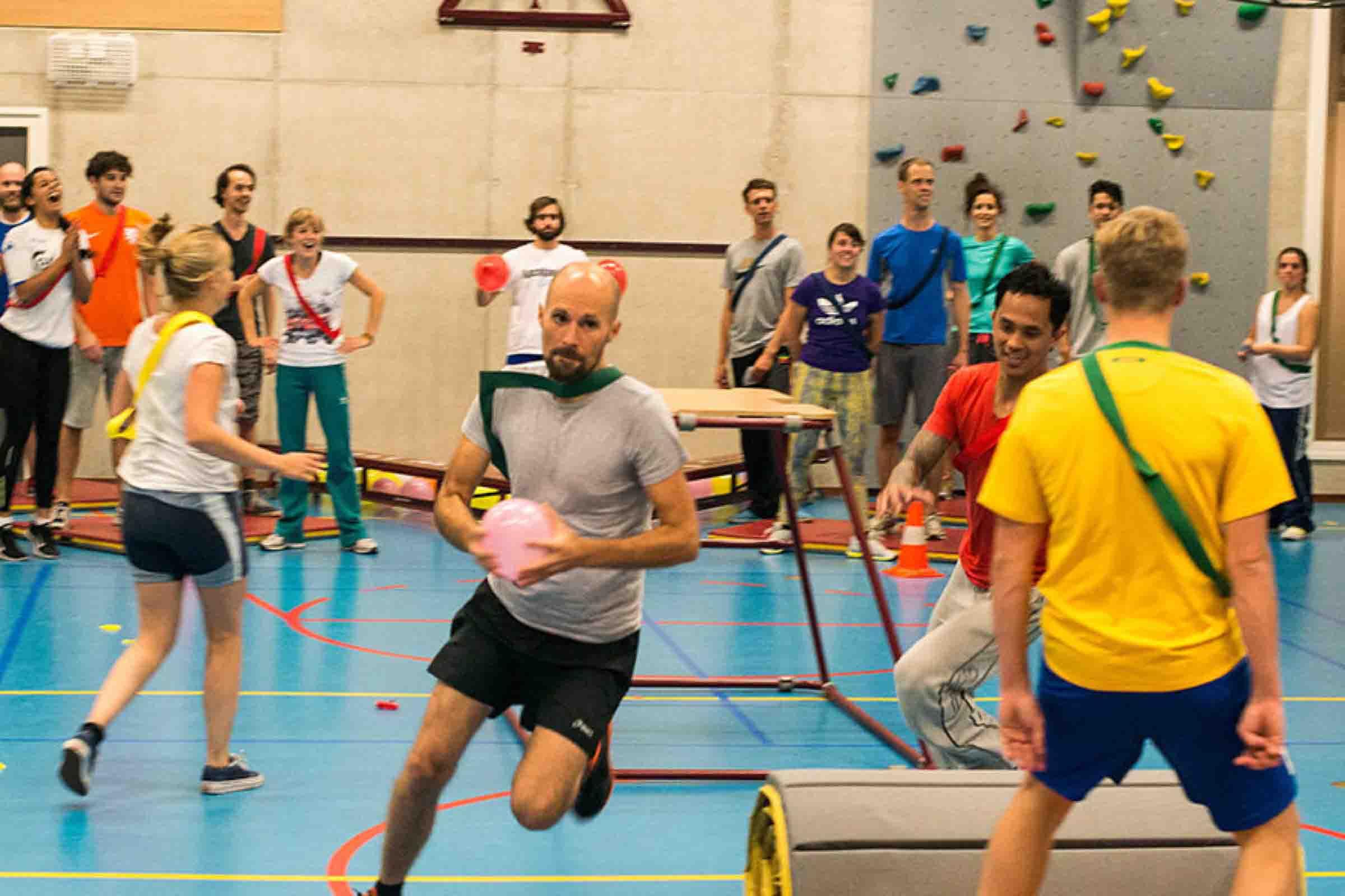 Een groep mensen die aan het apennkooien is in een gymzaal