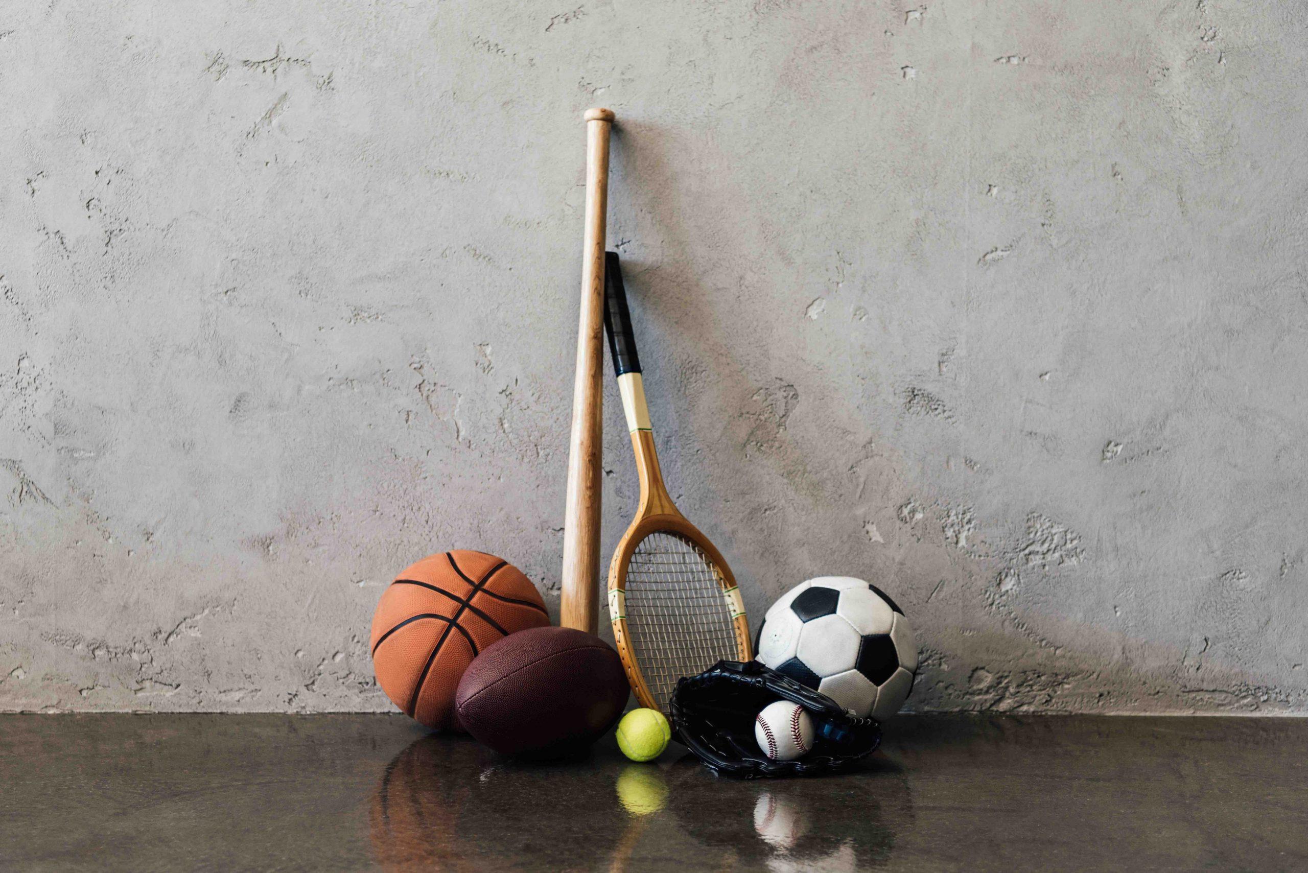 Een aantal sportattributen en ballen tegen een grijze muur